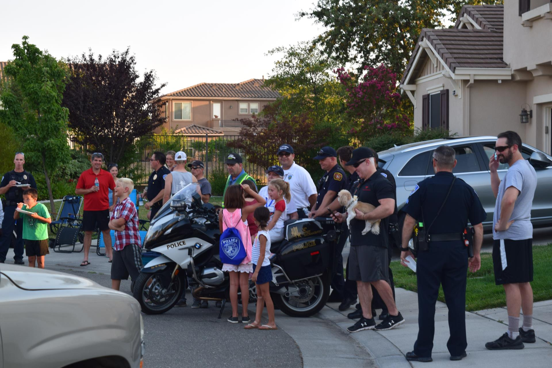 neighbors interacting with policemen, kids sitting on motorcycle at West Sacramento national night out event