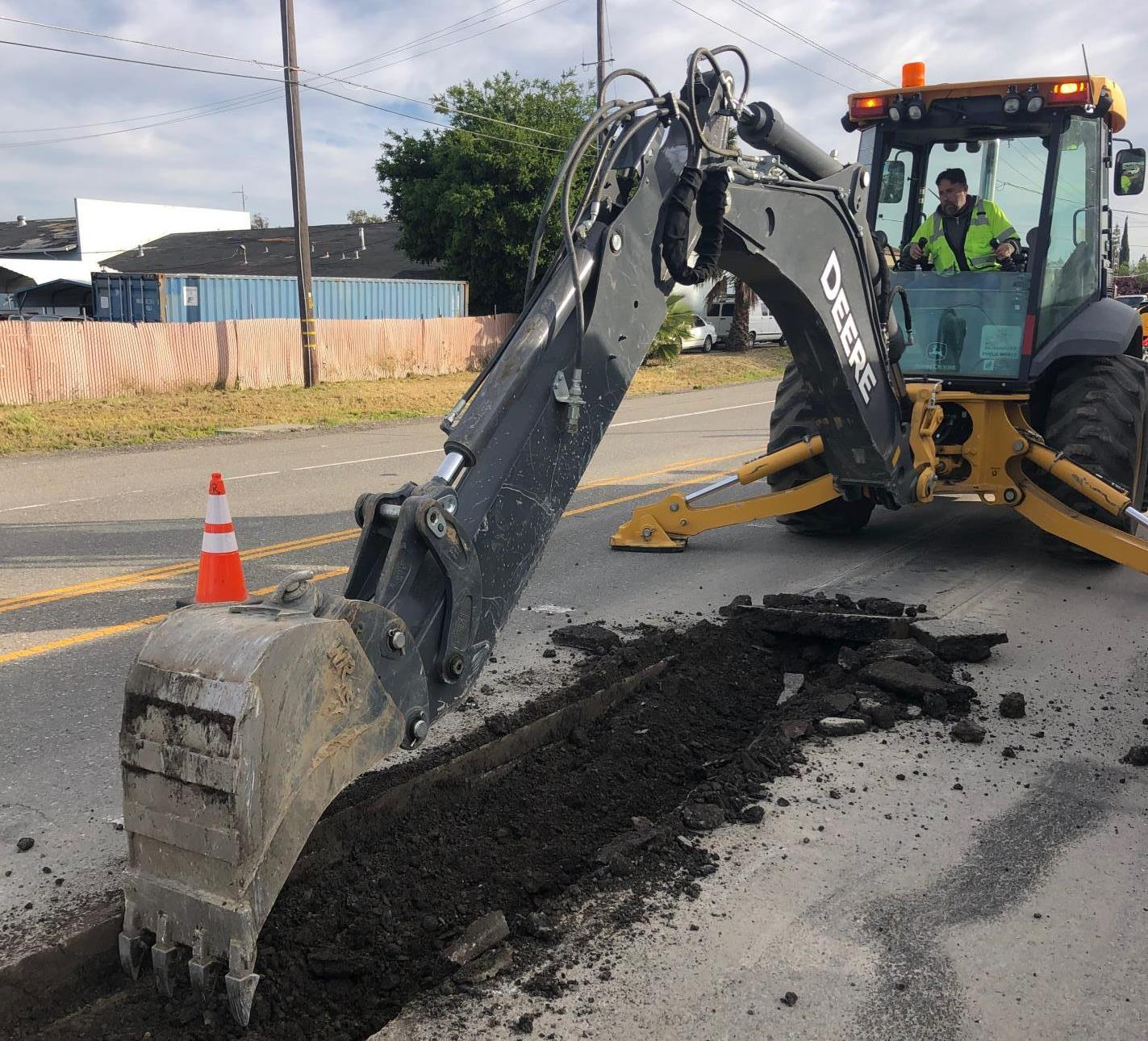public works crews use equipment to fix road