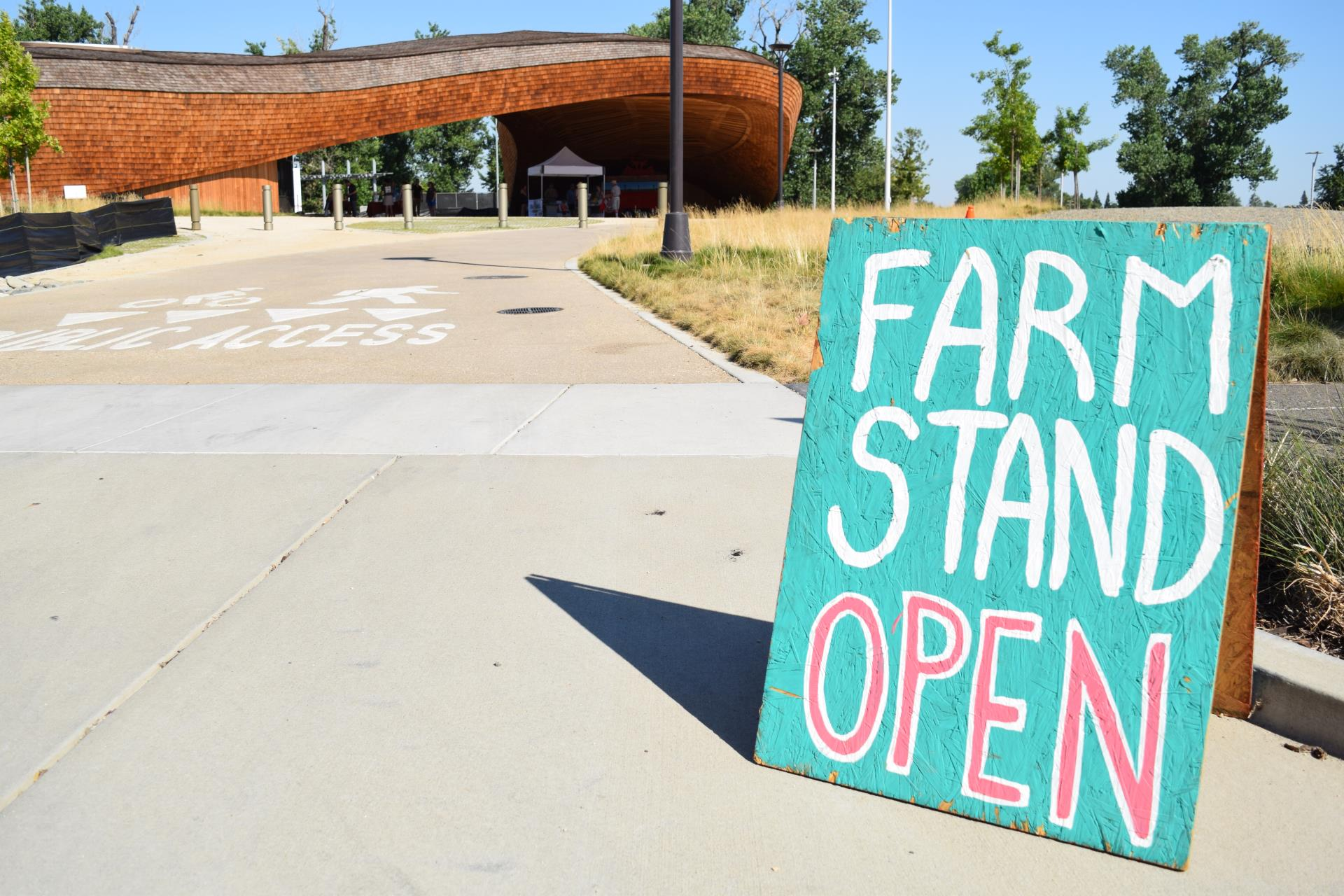 farm stand sign in front of the barn