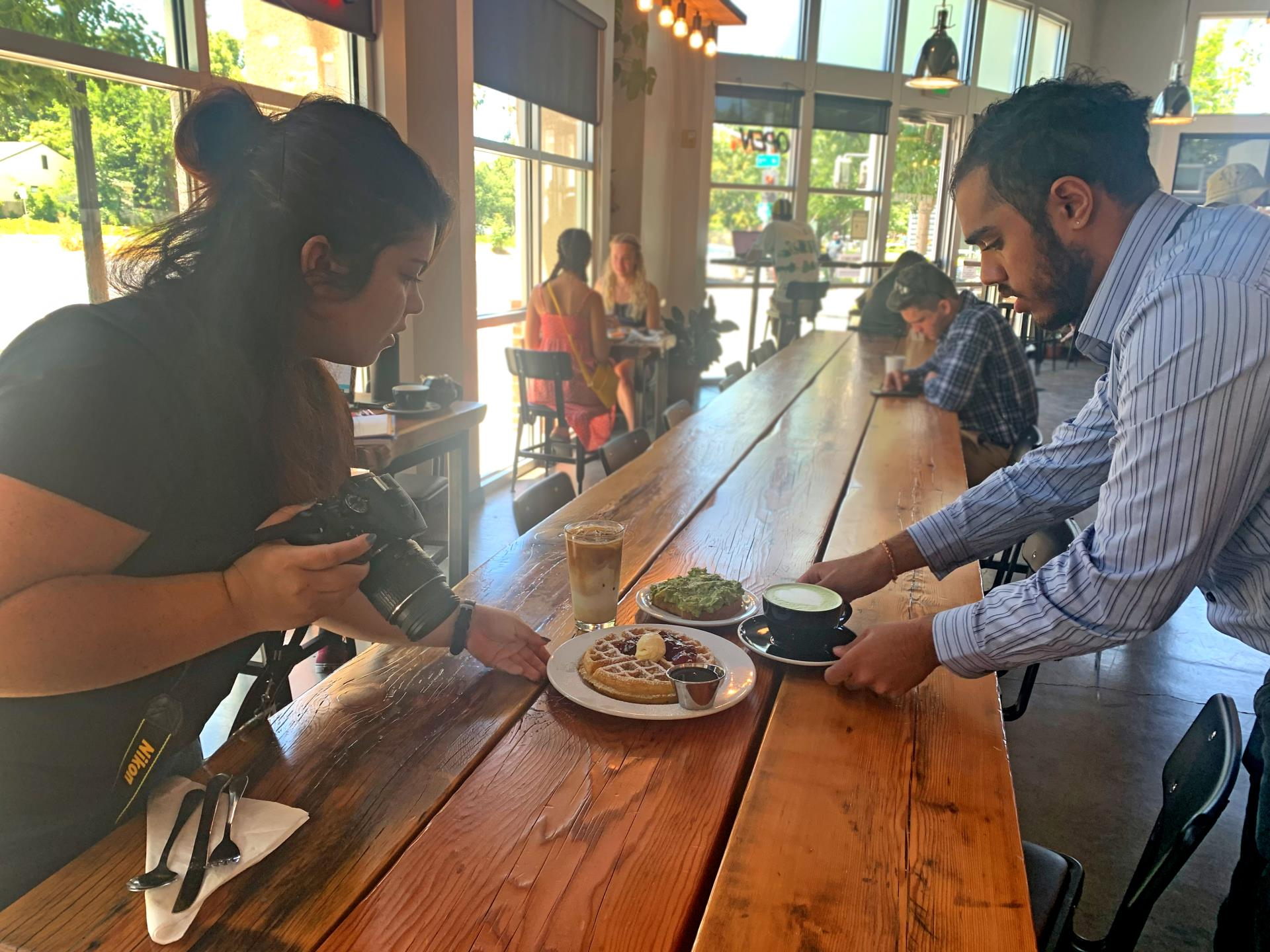 Tariana and Ravi taking Foodie Friday photos at Westside Coffee