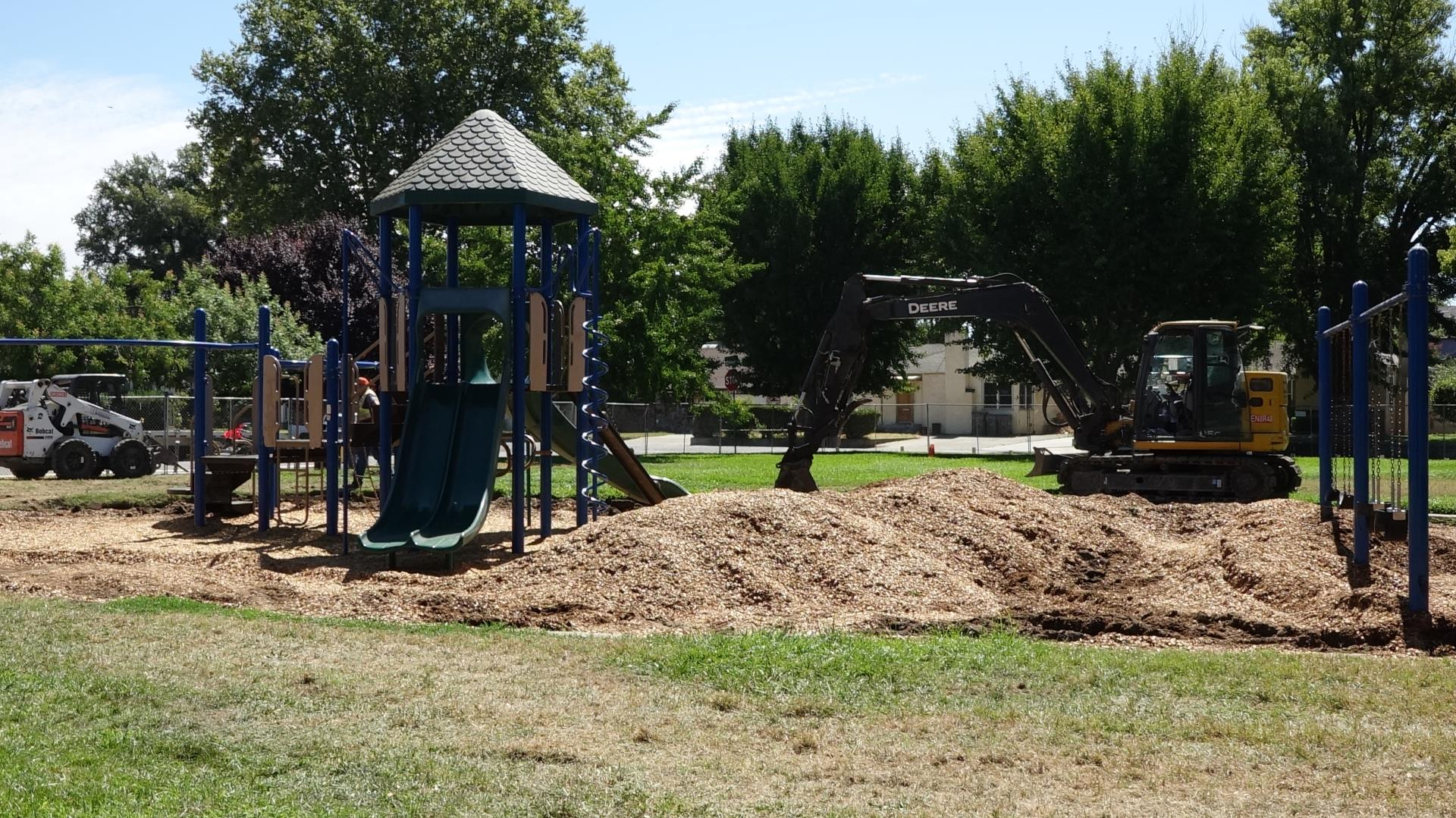 Memorial Park under rehabilitation with giant holes in the woodchips and a digger behind the park