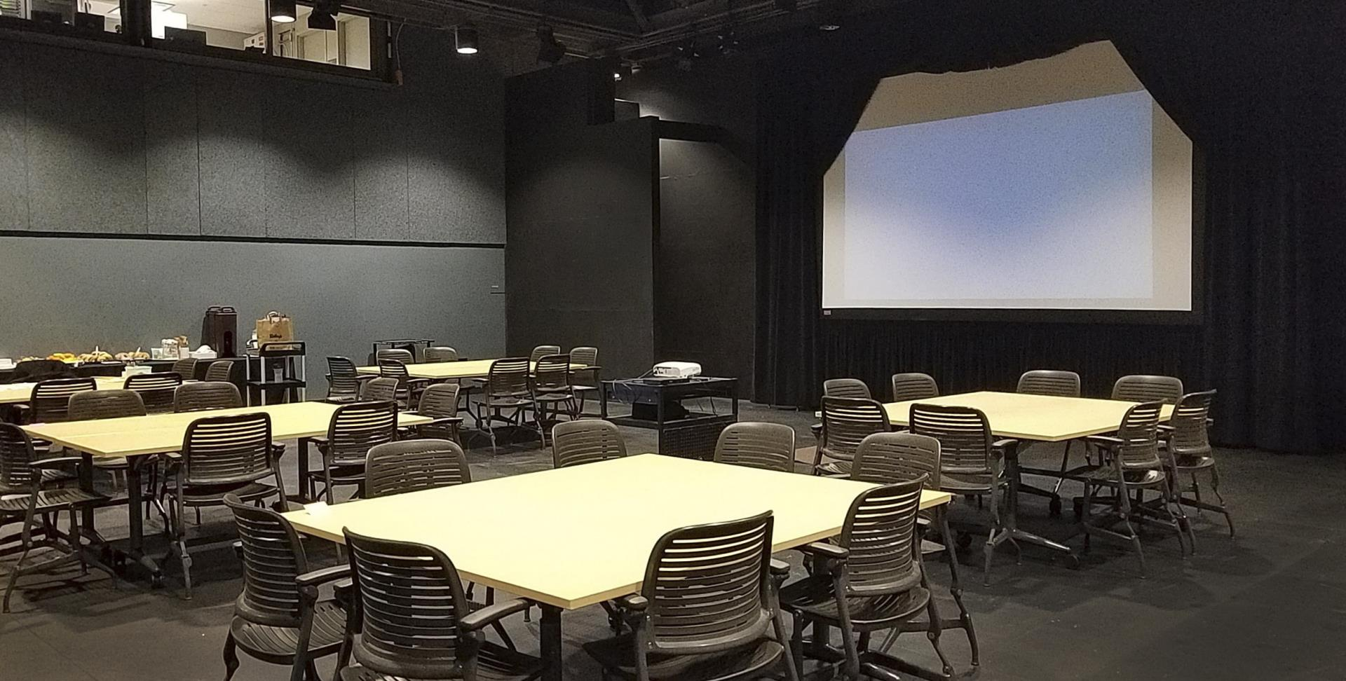 Workshop setup with tables and large screen
