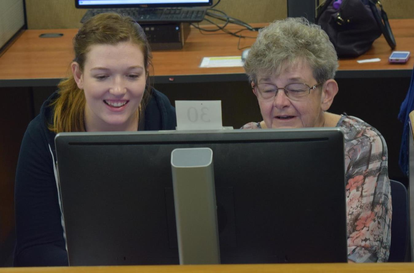 intern volunteers at computer class for adults